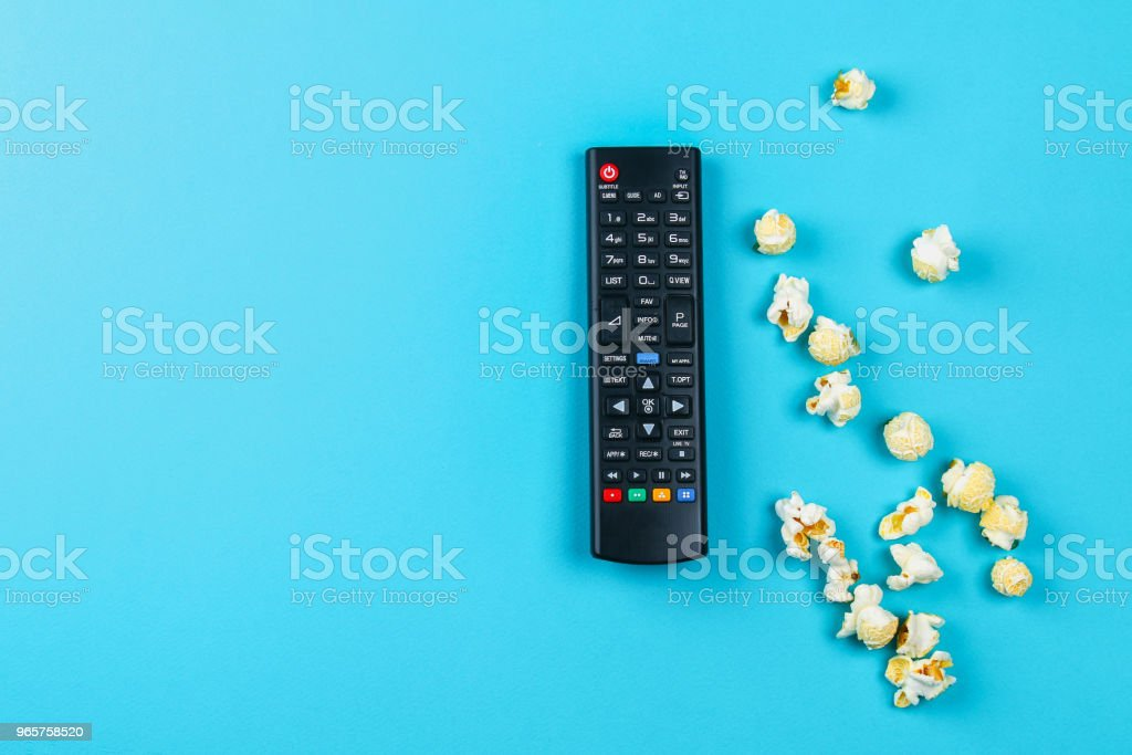 Box of popcorn spilled on blue background. - Royalty-free Art Stock Photo