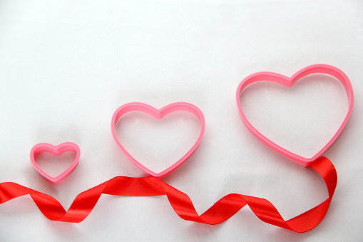 the box of red and pink hearts chocolates on white background with red ribbon, Valentine's Day, advertising banner