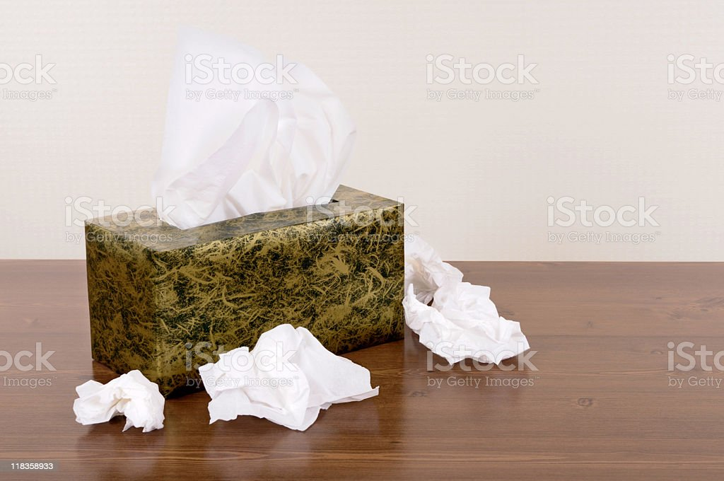 Box of tissues surrounded by used tissues stock photo