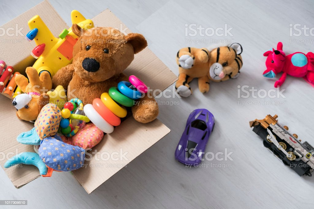 box of toys on the floor. Teddy bear in box,vintage tone. charitable contribution. donation. beneficence stock photo