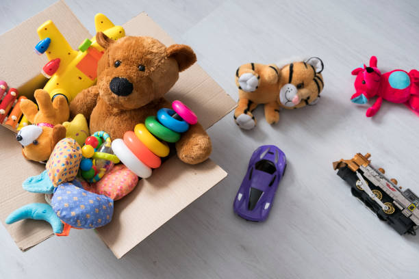 box of toys on the floor. teddy bear in box,vintage tone. charitable contribution. donation. beneficence - toy stock pictures, royalty-free photos & images