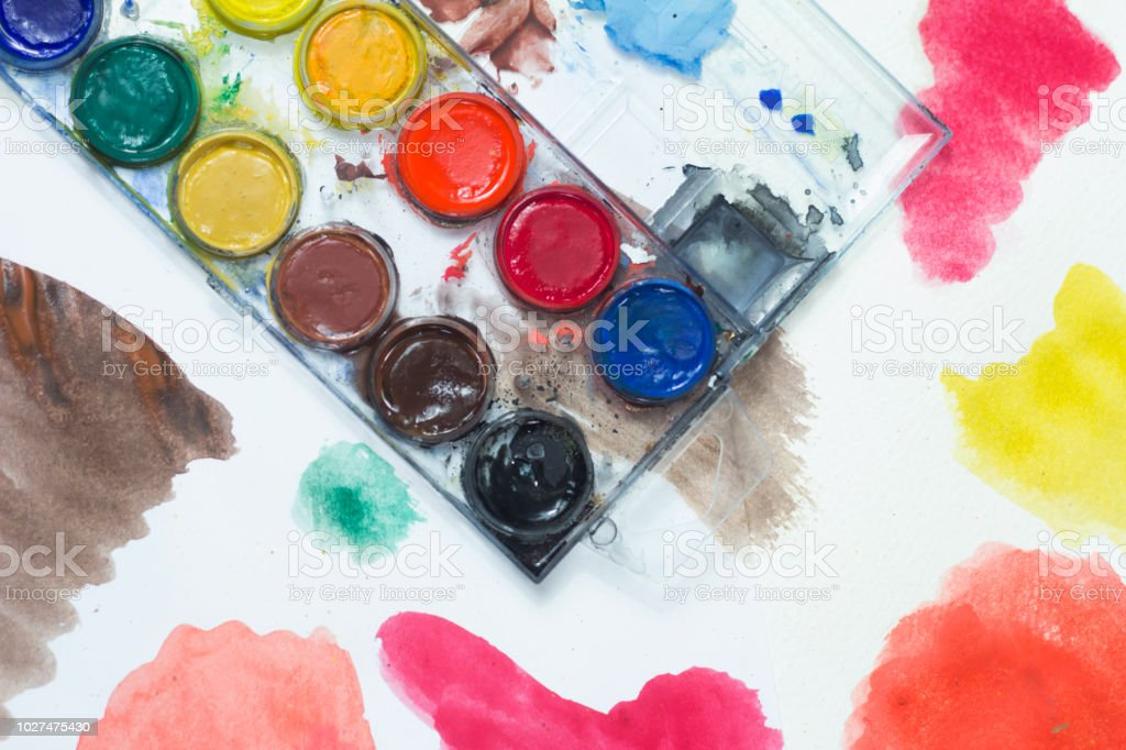 box of watercolors and brush exemplifying some strokes on paper stock photo