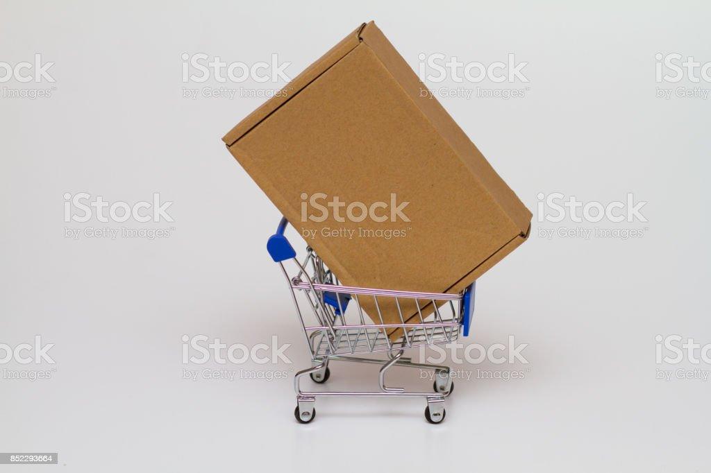 Box on a tiny Shopping Cart  on white background stock photo
