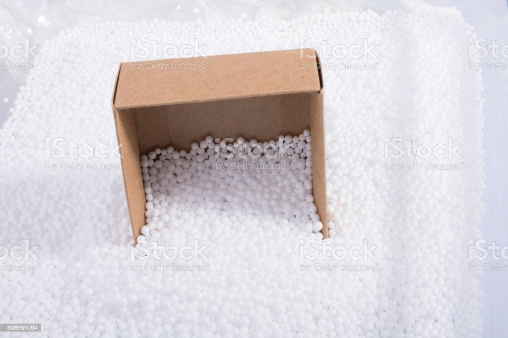Box on white polystyrene foam balls stock photo