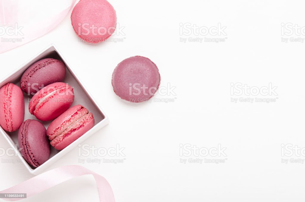 Box with colorful macaroons on a white background with ribbons. Sweet...