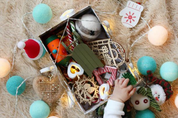 box mit bunten holz und filz weihnachtsdekorationen und weihnachtsbeleuchtung mit der hand des kleinen kindes auf einer weichen beige decke, top-ansicht. - filz kugel girlande stock-fotos und bilder