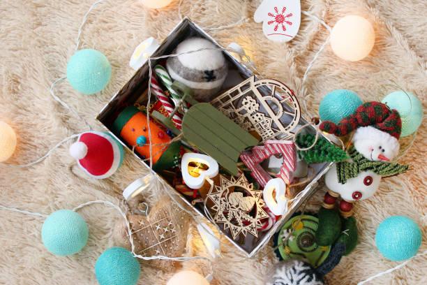 box mit bunten holz und filz weihnachtsdekorationen, karamell-sticks und weihnachtsbeleuchtung auf einer weichen beige decke, top-ansicht. - filz kugel girlande stock-fotos und bilder