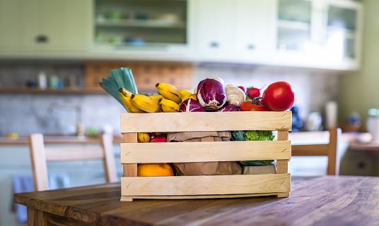 Box full of organic vegetables and fruits (tomatos, radish, zucchini, oranges, apples, radicchio, broccoli, bananas, edible mushrooms) on a kitchen table.
