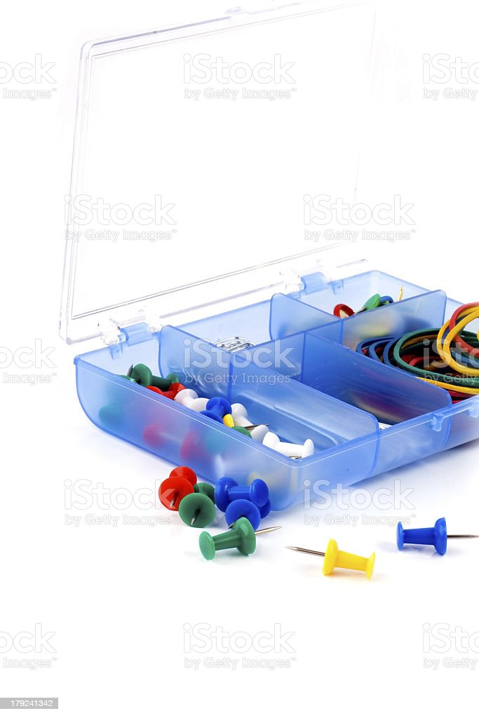 box with paperclips and pushpins on a white background royalty-free stock photo