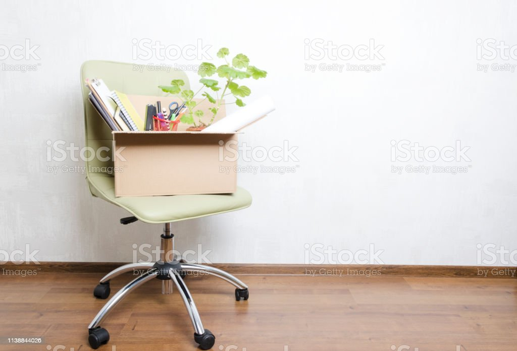 Box with personal items standing on the chair in the office.Concept of moving or dismissal Chair and box with different stuff in it, male hand holding blank speech bubble for your text.Concept of moving/fired from job Advertisement Stock Photo