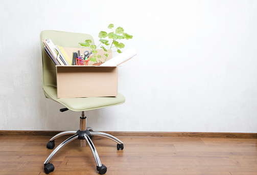 Box With Personal Items Standing On The Chair In The Officeconcept Of Moving Or Dismissal Stock Photo - Download Image Now
