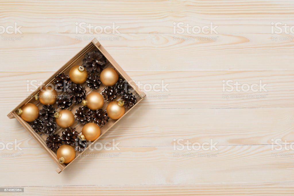 Box with pine cones and gold balls on a white wooden background. Top view. Flat lay. stock photo