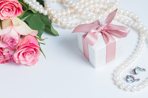 Gift box with pink ribbon with jewellery and roses on white table