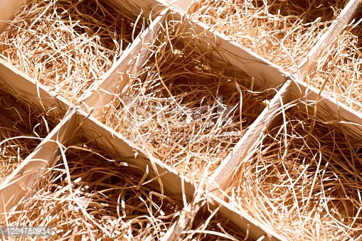 A box with straw for transporting vegetables and fragile items. Background texture