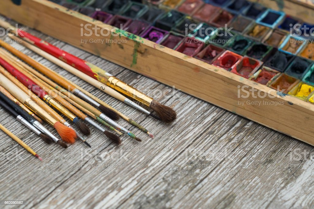 Box with watercolors and brushes on a wooden surface royalty-free stock photo