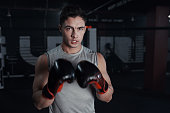 Portrait of a young man practicing his boxing routine at a gym