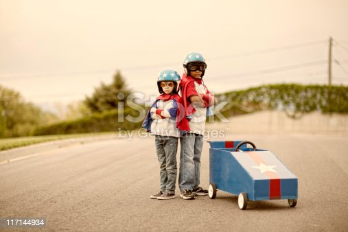 Two young boy racers next to their racing boxcar, ready for speed.