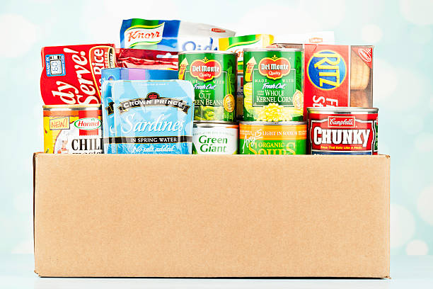 "Boxed Groceries For Food Drive ""Suffolk, Virginia, USA - August 16, 2012: A horizontal studio shot of a cardboard box filled with an assortment of non-perishable food items purchased from American grocery stores. Items include, canned goods from Del Monte, Campbell's, Hormel, Green Giant and Amy's, and packaged goods from Nabisco, Knorr, Crown Prince, Kraft and Minute."" food drive stock pictures, royalty-free photos & images"