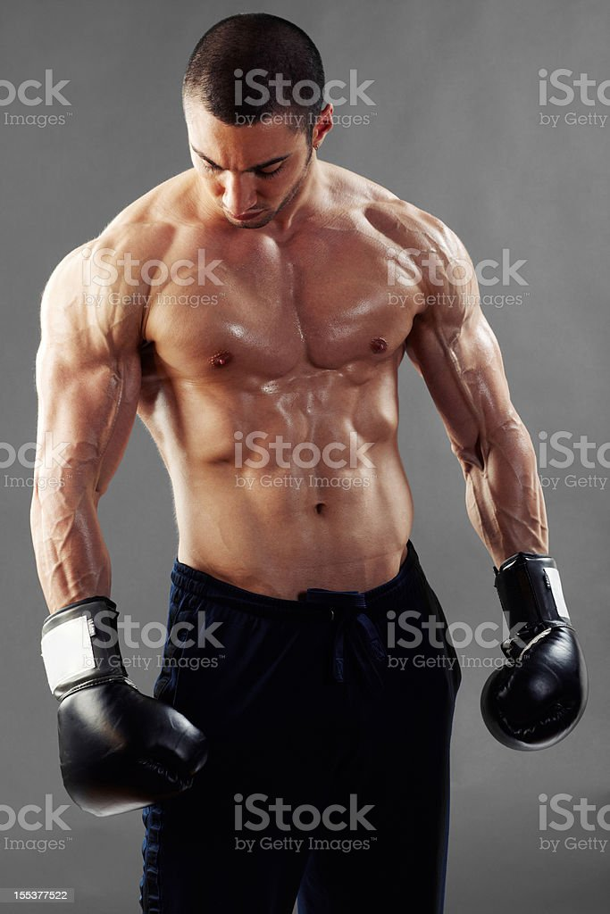 Boxer flexing muscles looking down royalty-free stock photo