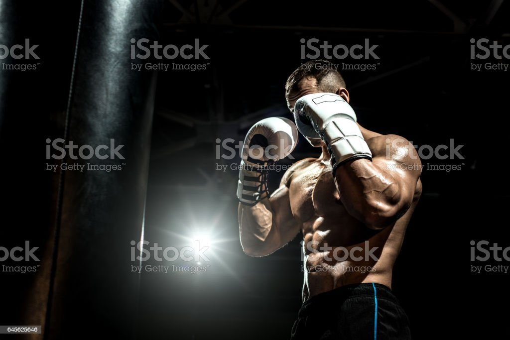 boxer in gym with punching bag stock photo