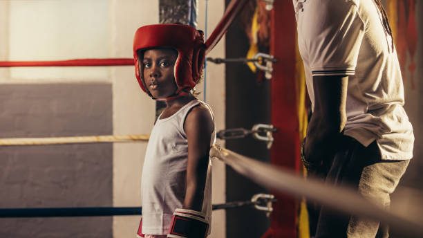 Boxer kid standing in the boxing ring stock photo