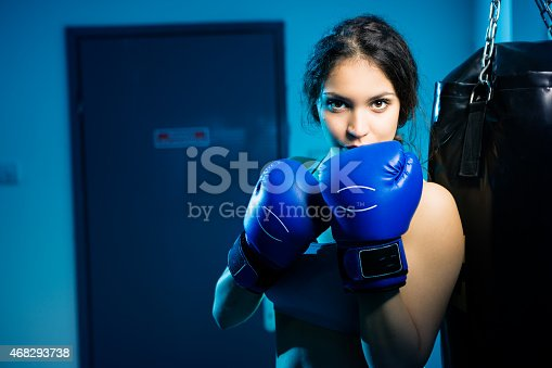 Beautiful woman posing with blue gloves, boxing in the gym. Canon 5D MK III