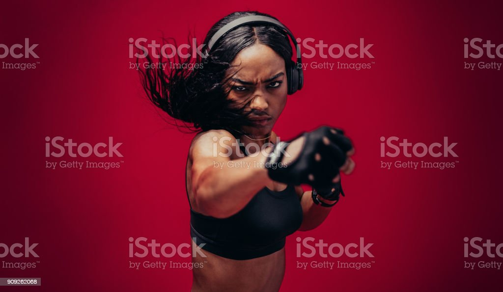 Boxer practicing her punches in a studio royalty-free stock photo