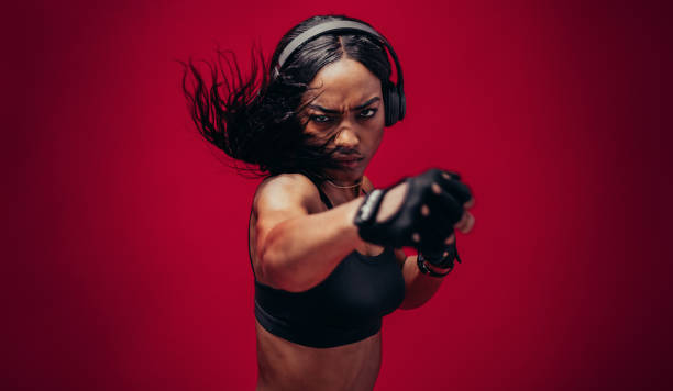 Boxer practicing her punches in a studio Boxer practicing her punches in a studio. African female boxer practicing boxing against red background. aggressively stock pictures, royalty-free photos & images