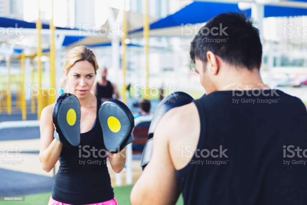 Boxer practicing with his female personal trainer stock photo