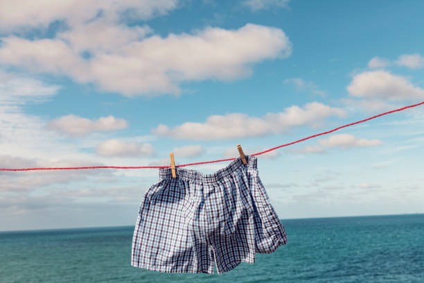 boxer shorts on a washing line overlooking the sea. - washing line stock photos and pictures