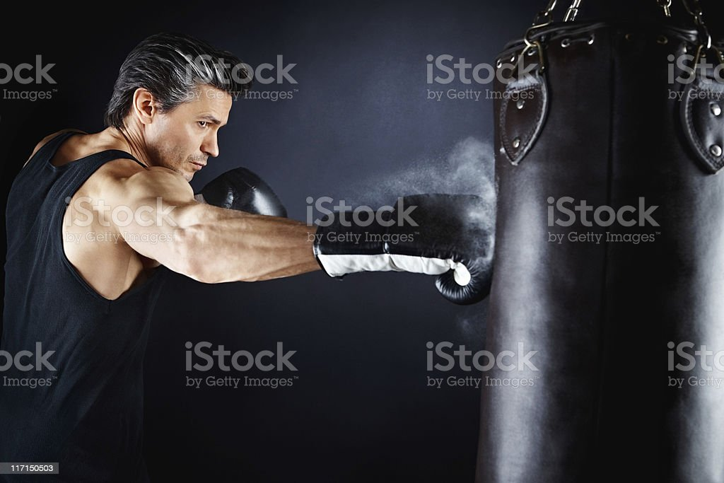 Boxer throwing powerful punch to bag royalty-free stock photo