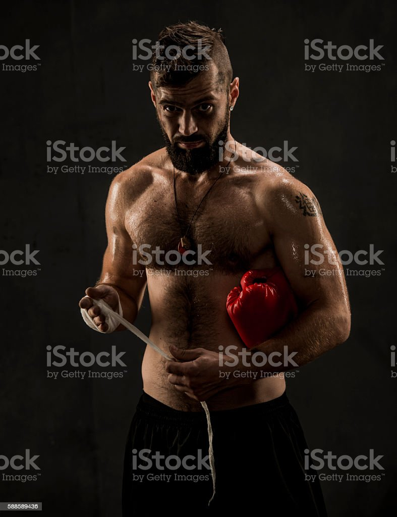 Boxer tying tape around his hand preparing to fight stock photo