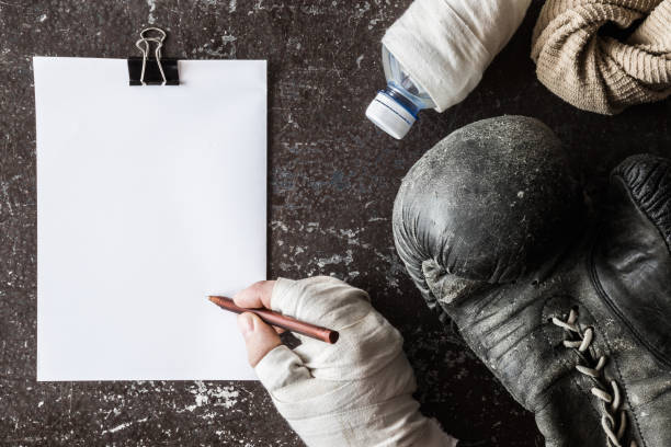 Boxer's hand in the boxing wrap signing a professional finance contract. Old boxing glove, towel and water bottle. Sport concept. Vintage retro style. Empty place for a text on the white paper. stock photo