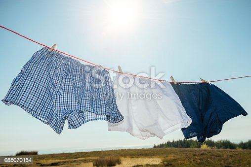 three pairs of boxer shorts on a washing line blowing in the wind, sun shining into camera causing lens flare.