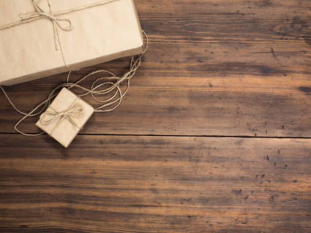 boxes in craft paper, eco paper on the wooden table. top view. parcels or gifts tied with twine. brown paper wrapped gift box with rope bow on a old rustic wood background - top view, wood table, empty imagens e fotografias de stock