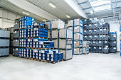 Horizontal image of a modern new warehouse of large factory. The warehouse is filled with boxes on pallets. Logistics, freight, shipping, receiving. No people, space for copy.