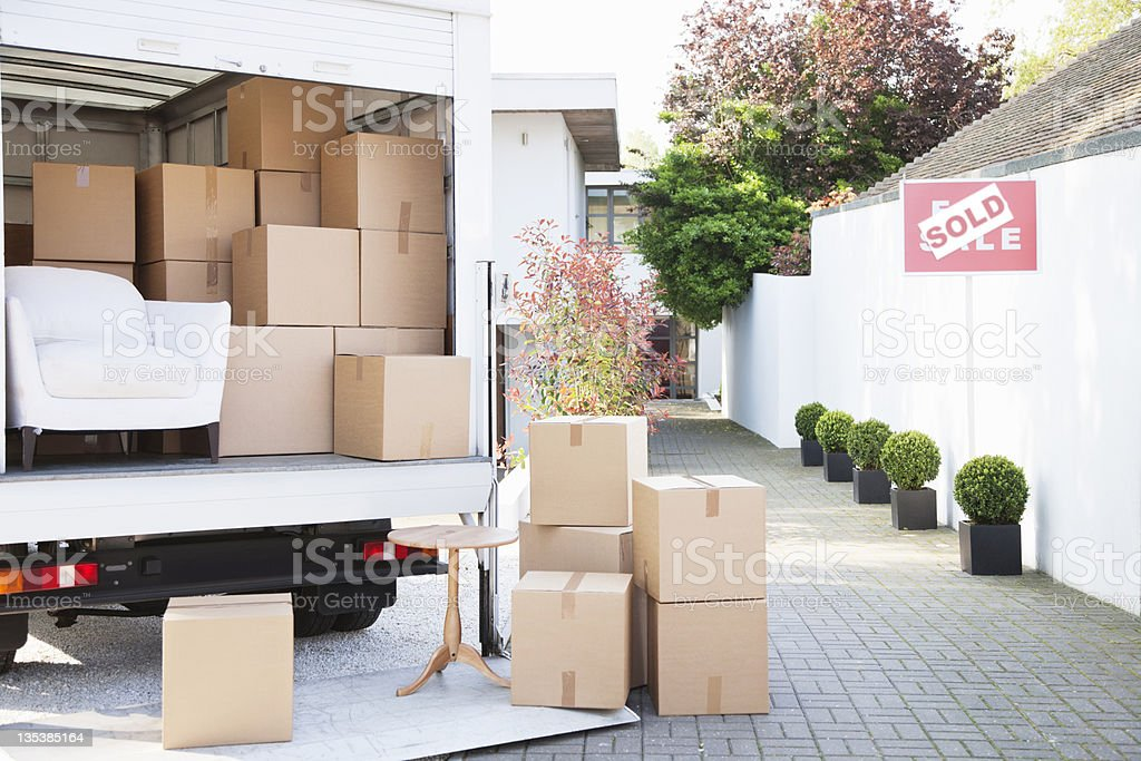 Boxes on ground near moving van stock photo
