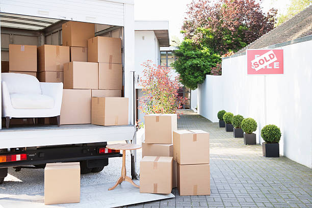 boxes on ground near moving van - relocation stock photos and pictures