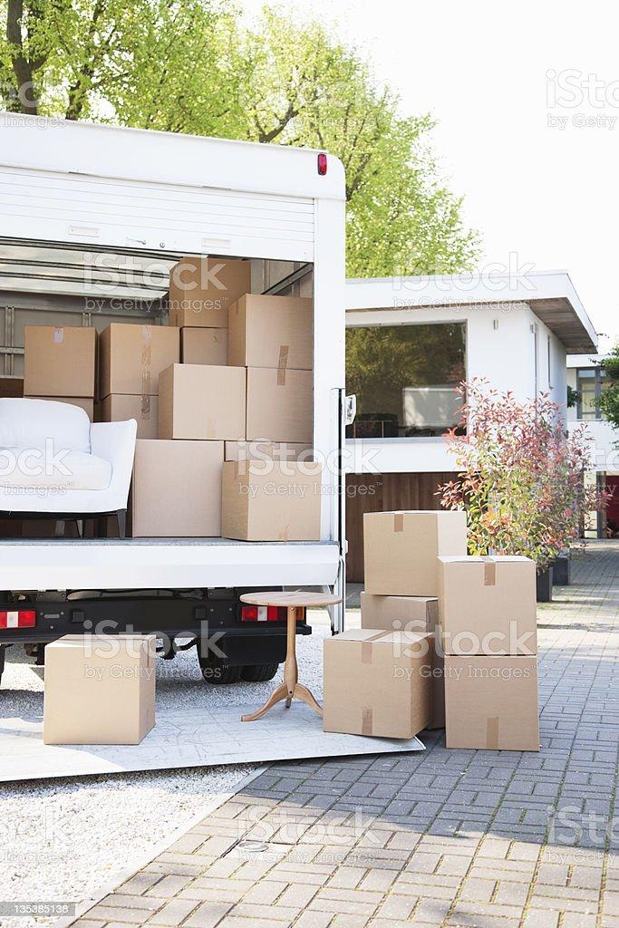Boxes on ground next to moving van stock photo