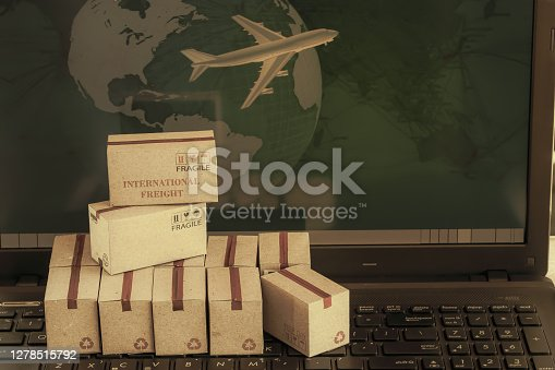 Boxes product on notebook keyboard. business concept of transportation, logistics, global shipping, international freight, overseas trade, regional, go to worldwide