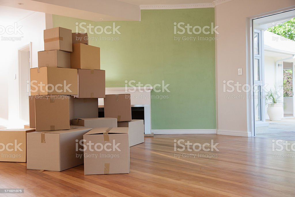 Boxes stacked in living room of new house stock photo