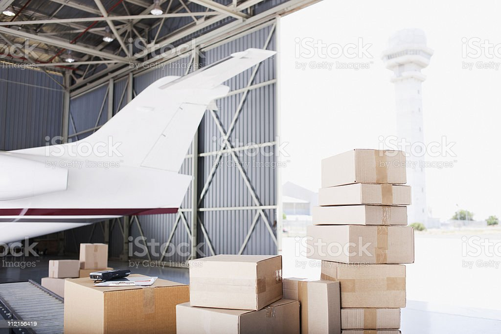 Boxes stacked near airplane in shipping area royalty-free stock photo