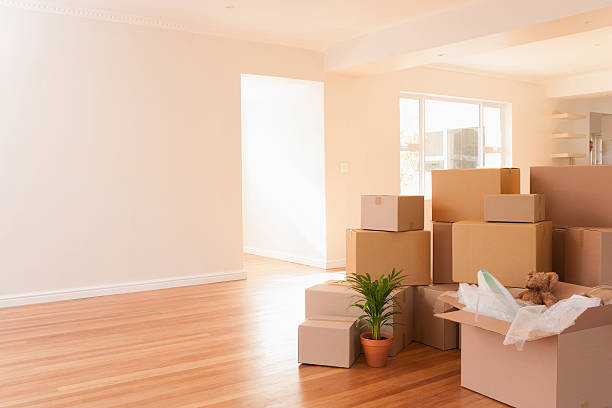 boxes stacked on wooden floor of new house - relocation stock photos and pictures
