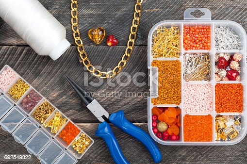 1074436306istockphoto Boxes with beads, spool of thread, plier, chain and glass hearts to create hand made jewelry on old wooden background. Making bracelet or necklace. Handmade accessories. Top view 692549322