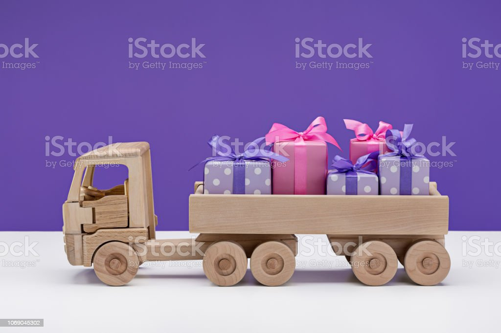 Truck with gifts in elegant paper on violet background with...