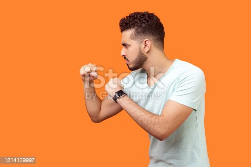 Boxing and self-defence. Side view of aggressive man keeping fists clenched, ready for fight. studio shot isolated on orange background