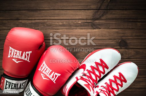 Florence, Italy - September 29, 2015: Close up of red boxing apparel equipment on a plank table, the shoes are Nike Hyperdunk with Everest boxing gloves. Studio shot.