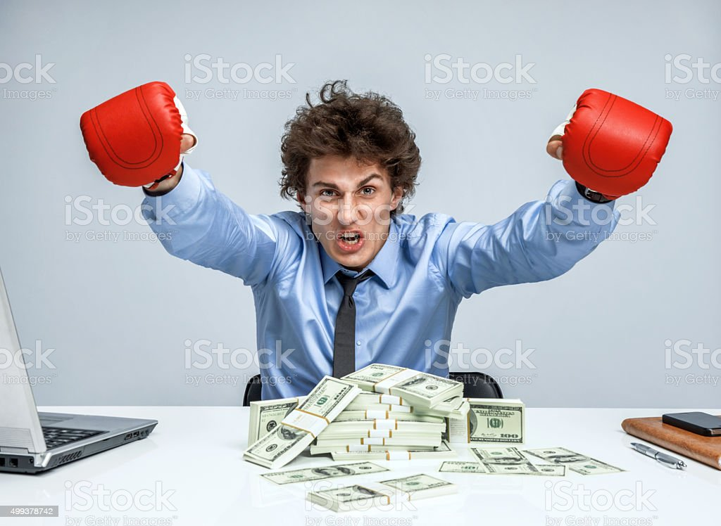 Boxing Businessman with a lot of money on the table stock photo