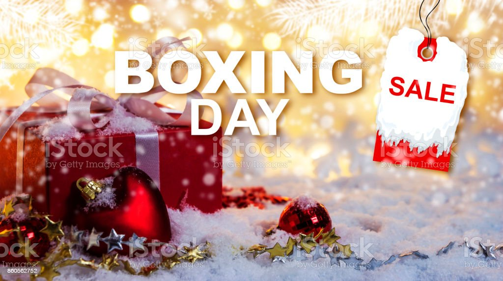 Boxing day sale concept of red gift box on snow with bokeh background stock photo
