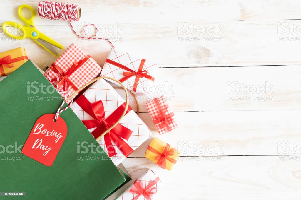Boxing day Sale text on a black tag with shopping bag and gift box on a wooden white background. Online Shopping concept. stock photo